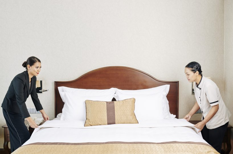 Asian manager of the hotel making the bed together with maid in the hotel room before the guest's arrival